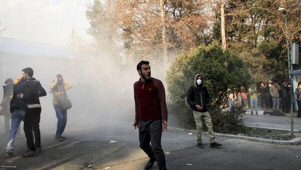 Iran, university students attend a protest inside Tehran University while a smoke grenade is thrown by anti-riot Iranian police, in Tehran, Iran, Saturday, Dec. 30, 2017 - Sputnik International