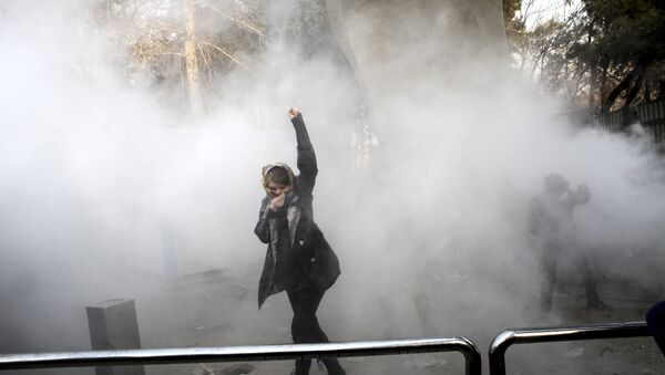FILE - In this Saturday, Dec. 30, 2017 file photo taken by an individual not employed by the Associated Press and obtained by the AP outside Iran, a university student attends a protest inside Tehran University while a smoke grenade is thrown by anti-riot Iranian police, in Tehran, Iran - Sputnik International
