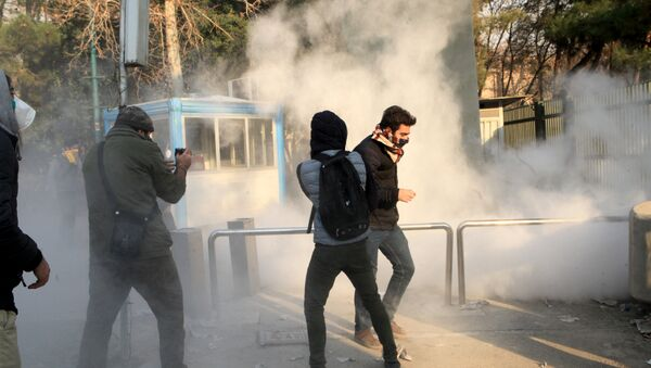 Iranian students run for cover from tear gas at the University of Tehran during a demonstration driven by anger over economic problems, in the capital Tehran on December 30, 2017 - Sputnik International