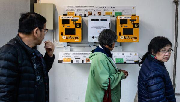 Pedestrians walk past ATM machines (L and R) for digital currency Bitcoin in Hong Kong on December 18, 2017 - Sputnik International