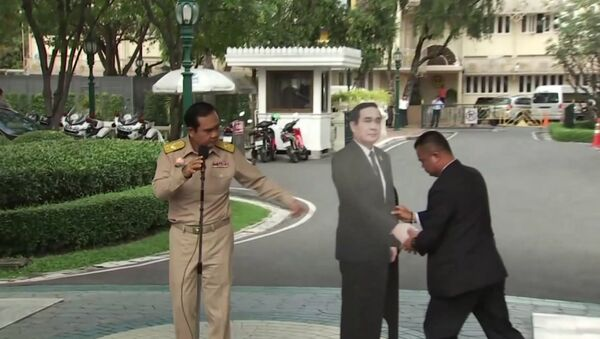 In this image from video, Thailand's Prime Minister Prayuth Chan-ocha, left, directs the scene as a life-sized cardboard cut-out figure of himself is carried into view by an aid, in Bangkok, Thailand, Monday Jan. 8, 2018. - Sputnik International