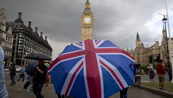 A pedestrian shelters from the rain beneath a Union flag themed umbrella as they walk near the Big Ben clock face and the Elizabeth Tower at the Houses of Parliament in central London. (File) - Sputnik International