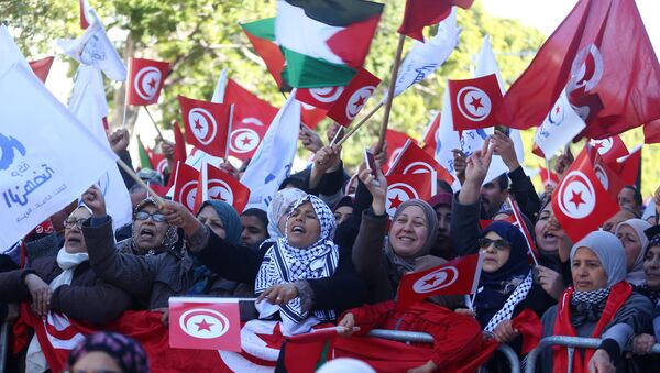People wave national flags during demonstrations on the seventh anniversary of the toppling of president Zine El-Abidine Ben Ali, in Tunis, Tunisia January 14, 2018 - Sputnik International