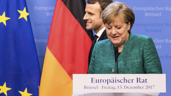 French President Emmanuel Macron, left, passes by German Chancellor Angela Merkel prior to addressing a media conference at an EU summit in Brussels on Friday, Dec. 15, 2017. - Sputnik International