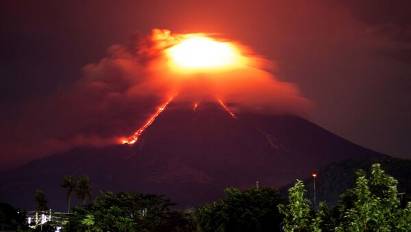 Lava cascades down the slopes of Mayon volcano as seen from Legazpi city, Albay province, around 340 kilometers (210 miles) southeast of Manila, Philippines, Monday, Jan. 15, 2018. More than 9,000 people have evacuated the area around the Philippines' most active volcano as lava flowed down its crater Monday in a gentle eruption that scientists warned could turn explosive. - Sputnik International