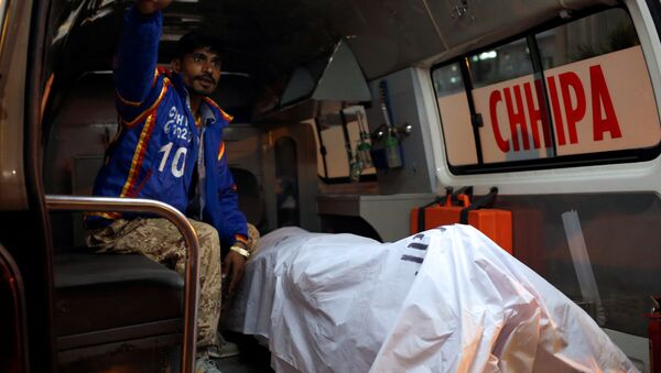 A rescue worker sits in an ambulance with a body of a Chinese man, working with a shipping company in Pakistan, who was shot dead on Monday in what police described as a targeted attack in Karachi, Pakistan February 5, 2018. - Sputnik International