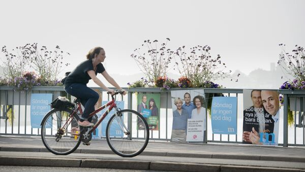 A girl on a bicycle passes general election posters for the Social Democrats party and the Moderaterna conservative party (right) in central Stockholm, Friday Sept. 12, 2014 (photo used for illustration purpose) - Sputnik International