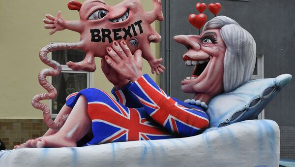 A float depicts British Prime Minister Theresa May looking at her Brexit-baby during the traditional Rose Monday parade in Duesseldorf, Germany - Sputnik International