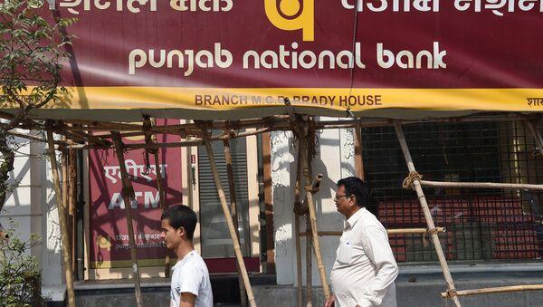 Indian men walk past signage for the state-owned Punjab National Bank (PNB) in Mumbai on February 14, 2018 - Sputnik International