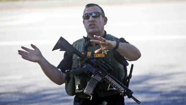 A law enforcement officer tells anxious family members to move back, Wednesday, Feb. 14, 2018, in Parkland, Fla. - Sputnik International