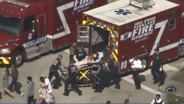 Rescue workers prepare to transport a victim on a stretcher near Marjory Stoneman Douglas High School following a shooting incident in Parkland, Florida, U.S. February 14, 2018 in this still image taken from a video - Sputnik International