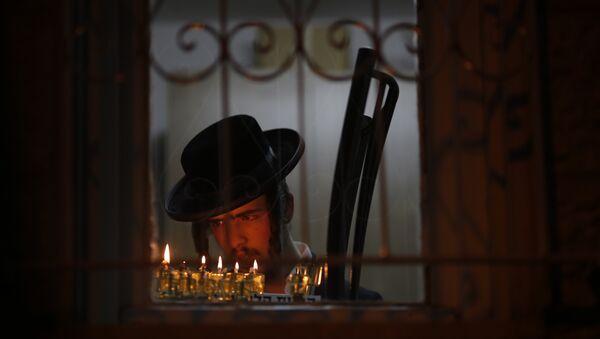 An ultra-Orthodox Jewish man lights candles during the Jewish holiday of Hanukkah in Jerusalem's Mea Shearim neighborhood in Jerusalem, Sunday, Dec. 17, 2017 - Sputnik International