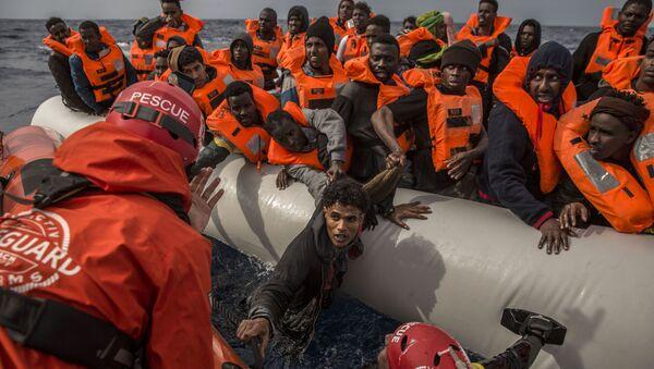 Спасение мигрантов сотрудниками испанской общественной организации Proactiva Open Arms с переполненной резиновой лодки у берегов Ливии - Sputnik International