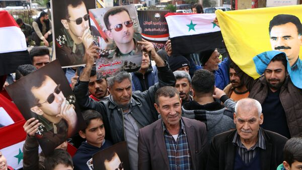 A picture taken on February 22, 2018 shows people waving the Syrian flag and portraits of President Bashar al-Assad and Kurdistan Worker's Party (PKK) leader Abdullah Ocalan as a convoy of pro-Syrian government fighters arrives in Syria's northern region of Afrin - Sputnik International