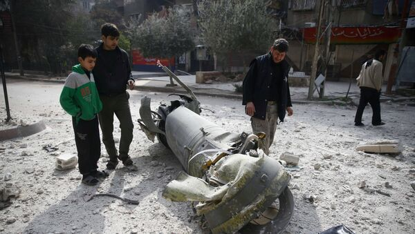 People inspect missile remains in the besieged town of Douma, in eastern Ghouta, in Damascus, Syria, February 23, 2018 - Sputnik International
