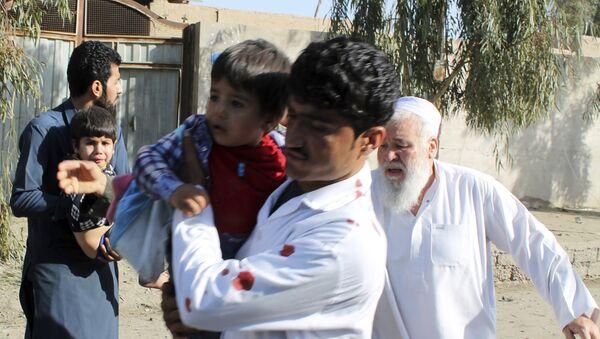 Men carry children away from an explosion site in Lashkar Gah, capital of southern Helmand province, Afghanistan, Saturday, Feb. 24, 2018 - Sputnik International