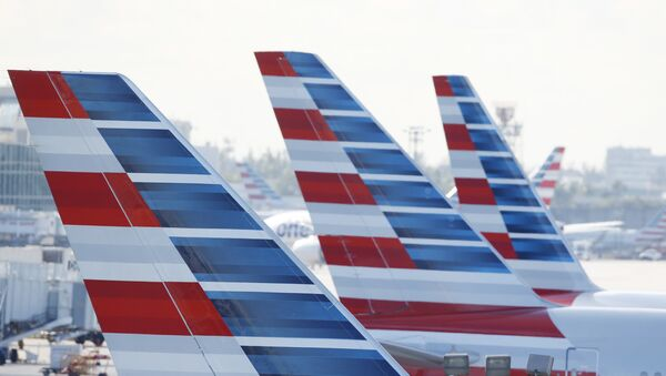 Painted vertical stabilizers are viewed as American Airlines jets are parked on the airport apron, Monday, Nov. 6, 2017, at Miami International Airport in Miami. American Airlines and a subsidiary will pay $9.8 million in stock to settle claims that they failed to help disabled employees return to work. - Sputnik International