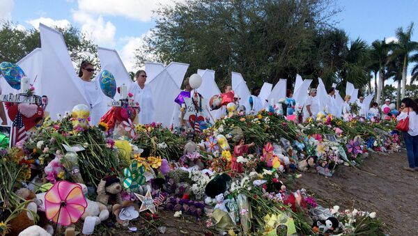 Seventeen people dressed as angels stand Sunday, Feb. 25, 2018, at the memorial outside Marjory Stoneman Douglas High School in Parkland, Fla., for those killed in a shooting on Feb. 14. - Sputnik International