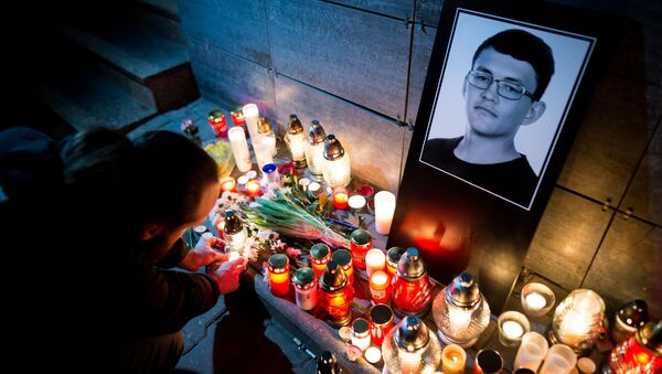 A man lits a candle in front of the Aktuality newsroom, the employer of the murdered investigative journalist Jan Kuciak, on February 26, 2018 in Bratislava - Sputnik International