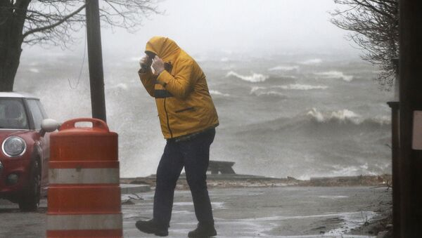 A pedestrian walks near the coastline Friday, March 2, 2018, in Newburyport, Mass. as a major nor'easter pounds the East Coast, packing heavy rain, intermittent snow and strong winds. - Sputnik International