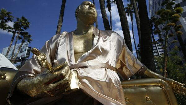A golden statue of a bathrobe-clad Harvey Weinstein, seated almost regally atop a couch holding a fake Oscar Statuette, takes up temporary sidewalk residence four days before the Oscars on Hollywood Blvd. in Los Angeles Thursday, March 1, 2018. - Sputnik International