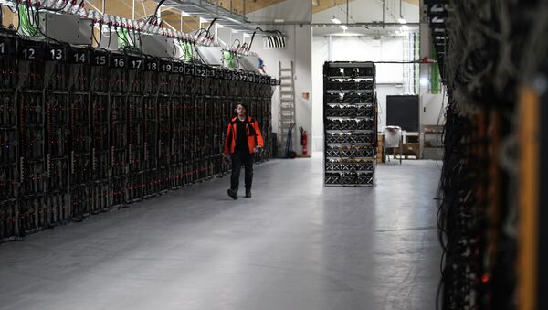 In this photo taken on Jan. 17, 2018, a worker walks along a row of computer rigs that run around the clock 'mining' bitcoin inside the Genesis Mining cryptocurrency mine in Keflavik, Iceland - Sputnik International