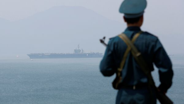 A Vietnamese soldier keeps watch in front of U.S. aircraft carrier USS Carl Vinson after its arrival at a port in Danang, Vietnam March 5, 2018 - Sputnik International