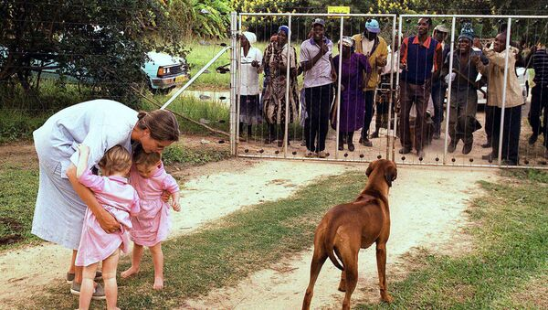 In this file photo dated March 29, 2000, Pippa van Rechteren, left, and her two-year-old twins Catherine, second from left, and Elisabeth, third from left, are blocked from leaving their house on the white-owned commercial farm, Chiripiro, by Zimbabwe war veterans in Centenary district, 150 kilometers (93 miles) north of Harare - Sputnik International