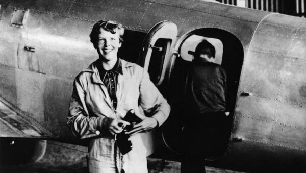 Amelia Earhart standing by her Lockheed Electra with Fred Noonan in the background - Sputnik International