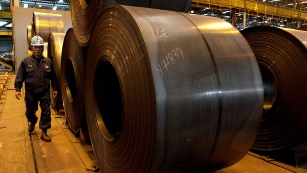 A worker walks by rolls of steel products at Posco steel mill in Pohang, south of Seoul, South Korea, Friday, Dec. 5, 2003 - Sputnik International