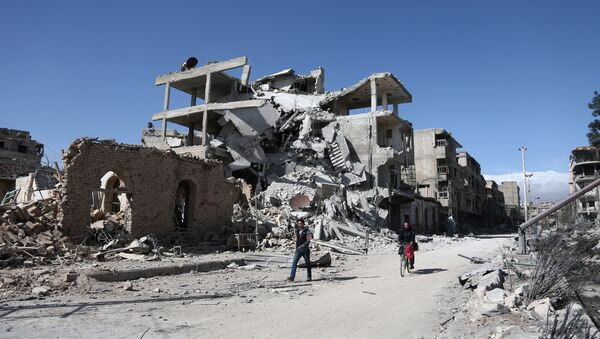 Syrians walk past destroyed buildings in the rebel-held town of Hamouria, in the besieged Eastern Ghouta region on the outskirts of the capital Damascus, on March 9, 2018 - Sputnik International