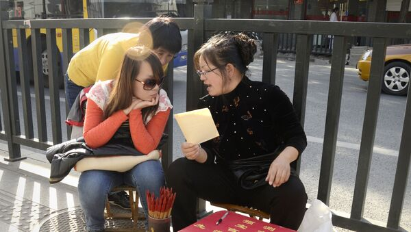 (File) A fortune-teller talks with two girls by a road in Beijing on October 24, 2012 - Sputnik International