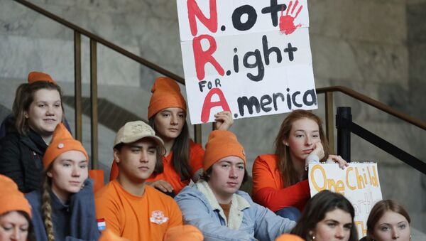 Lydia Ringer, 16, a junior at Roosevelt High School in Seattle, holds a sign that reads NRA - Not Right for America, Tuesday, March 6, 2018, as she attends a rally against gun violence at the Capitol in Olympia, Wash. The rally was held on the same day Gov. Inslee was scheduled to sign a bill banning the sale and possession of gun bump stocks in the state of Washington. - Sputnik International