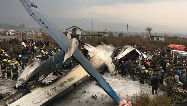 Nepalese rescuers stand near a passenger plane from Bangladesh that crashed at the airport in Kathmandu, Nepal, Monday, March 12, 2018 - Sputnik International