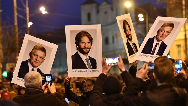 Protesters holds placards bearing faceted portraits of Slovakia's Prime Minister Robert Foco and Foreign Minister Robert Kalinak during a rally under the slogan For a Decent Slovakia, against corruption and to pay tribute to murdered Slovak journalist Jan Kuciak and his fiancee Martina Kusnirova on March 9, 2018 at the Slovak National Uprising (SNP) square in Bratislava, Slovakia - Sputnik International