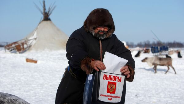 A herder of the agricultural cooperative organisation Harp casts his vote into a mobile ballot box during the early voting in remote areas ahead of the presidential election, at a reindeer camping ground, about 250 km south of Naryan-Mar, in Nenets Autonomous District, Russia, March 4, 2018 - Sputnik International