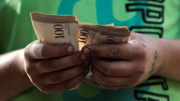 A cashier counts Venezuelan bolivar notes at a street market in downtown Caracas, Venezuela - Sputnik International