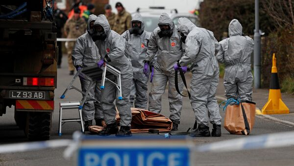 British Military personnel wearing protective coveralls work to remove a vehicle connected to the March 4 nerve agent attack in Salisbury, from a residential street in Gillingham, southeast England on March 14, 2018 - Sputnik International
