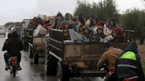 People sit in a truck with their belongings in the north east of Afrin, Syria March 15, 2018 - Sputnik International