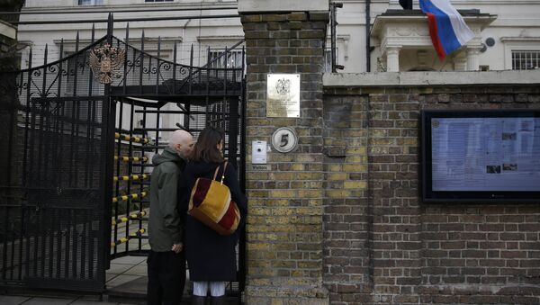 Two people wait to get into the Russian Embassy as a man works to untangle the national flag flown from the Russian Embassy, after it became entangled on its staff at the embassy in London, Wednesday, March 14, 2018 - Sputnik International