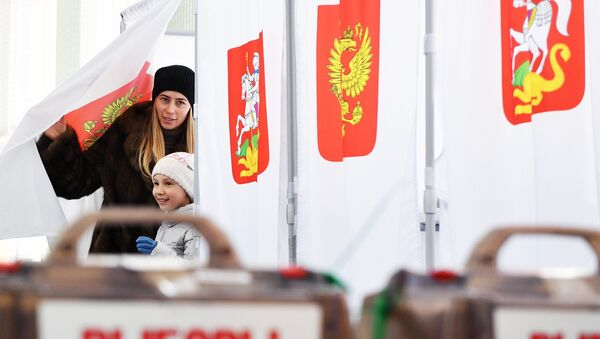 A woman with a child during the voting at the Russian presidential elections at polling station No. 13-06 in Moscow - Sputnik International