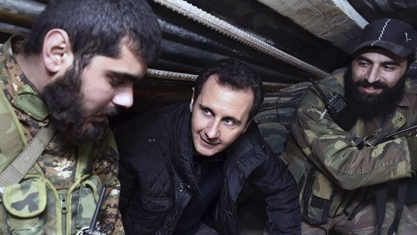 (File) This Wednesday, Dec. 31, 2014, file photo released by the Syrian official news agency SANA, Syrian President Bashar Assad, center, speaks with Syrian troops during his visit to the front line in the eastern Damascus district of Jobar, Syria - Sputnik International