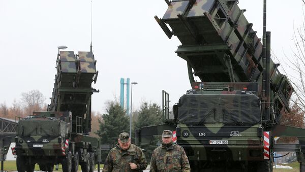Soldiers of the Air Defence Missile Squadron 2 walk past Patriot missile launchers in the background in Bad Suelze, northern Germany on December 4, 2012 - Sputnik International