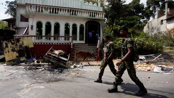 Sri Lanka's Special Task Force soldiers walk past a damaged mosque after a clash between two communities in Digana central district of Kandy, Sri Lanka March 8, 2018 - Sputnik International
