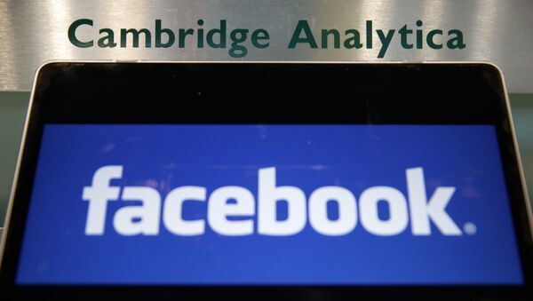 A laptop showing the Facebook logo is held alongside a Cambridge Analytica sign at the entrance to the building housing the offices of Cambridge Analytica, in central London - Sputnik International