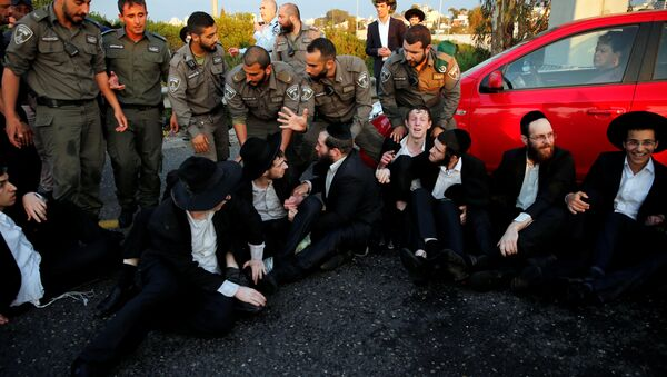 An Israeli ultra-Orthodox Jew block a main road in Israel before security forces evacuate them during a protest against the detention of a member of his community who refuses to serve in the Israeli army, in Bnei Brak, Israel - Sputnik International