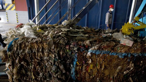 A worker walks past garbage being processed at the Majialou Garbage Transfer Station in Beijing, China, Thursday, March 30, 2017 - Sputnik International