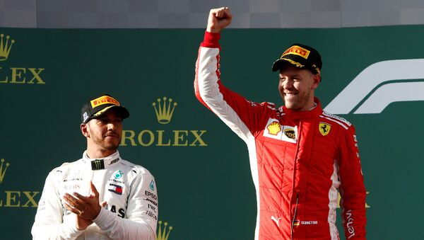 Formula One F1 - Australian Grand Prix - Melbourne Grand Prix Circuit, Melbourne, Australia - March 25, 2018 Ferrari's Sebastian Vettel celebrates his win on the podium with Mercedes' Lewis Hamilton - Sputnik International