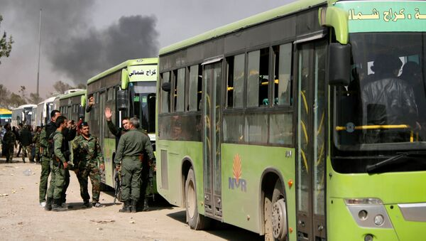 Members of Syrian forces of President Bashar al Assad stand next to buses carrying rebels and their families before they are evacuated, at Harasta highway outside Jobar, in Damascus, Syria March 25, 2018 - Sputnik International