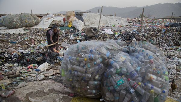 An Indian woman makes a drain for dirty water to pass next to plastic bottles collected for recycling at a garbage dumping site in Gauhati, India, Wednesday, Mar 7, 2018 - Sputnik International